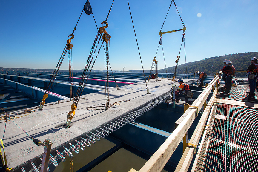 Workers make final adjustments as a high-strength road deck panel is positioned for the new bridge.