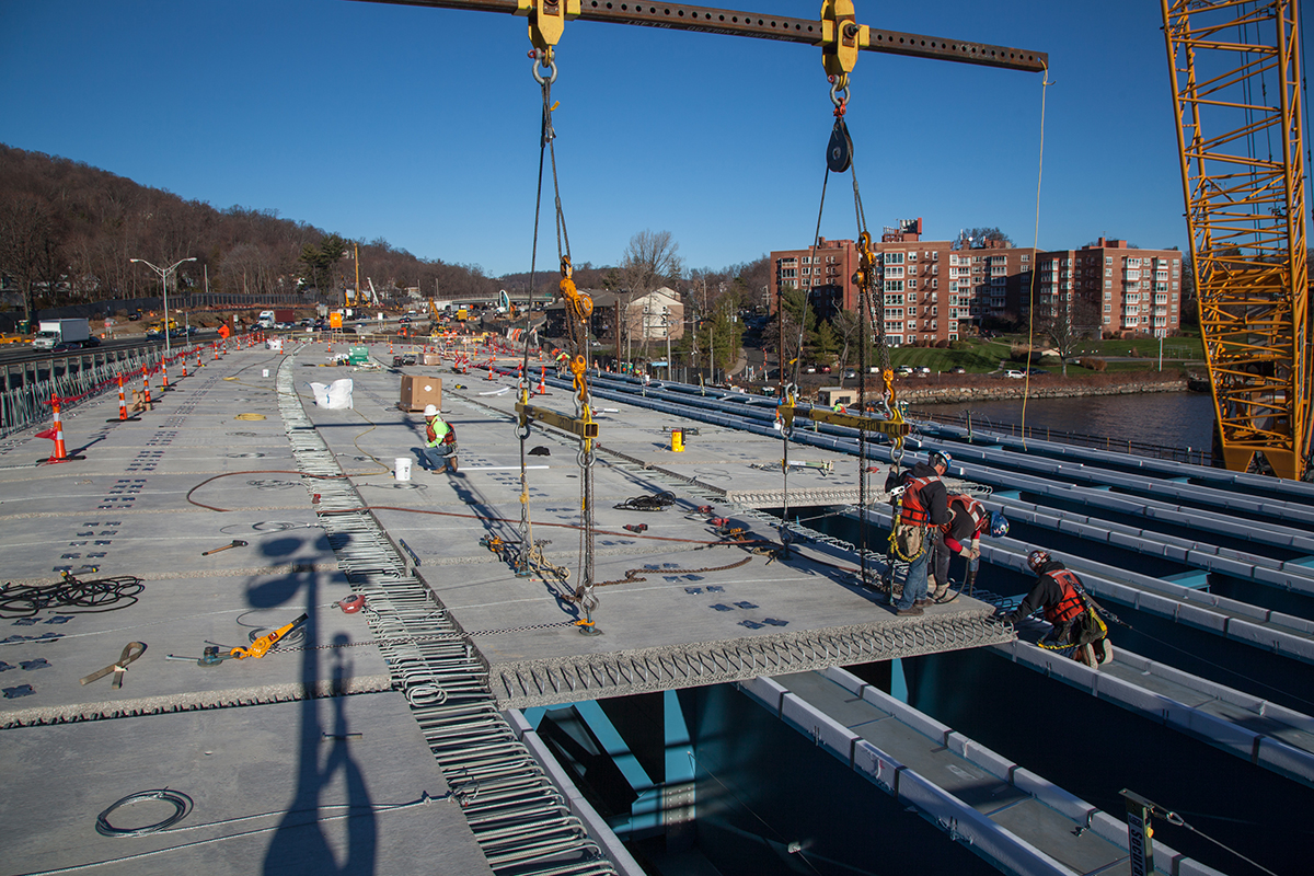 The new road deck panels rest atop the previously installed steel-blue girders.